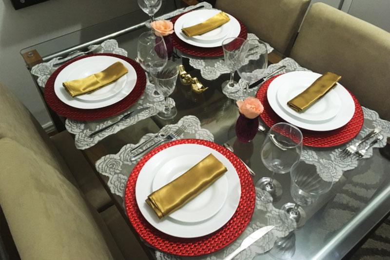 Mesa posta para jantar com guardanapo dourado e sousplat vermelho