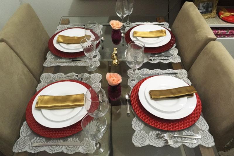 Mesa posta nas cores vinho, dourado e branco, com jogo americano de renda